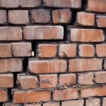 Large and wide crack in the wall of red brick